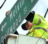 Working on Lynn Garden Drive, Judd Moore hangs new sign as the Kingsport Traffic Dept continues to change street signs around the city to comply with changes in federal regulations. Photo by Ned Jilton II