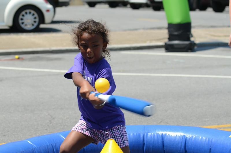 Kamaya Greene swings at a plastic ball in the kid's zone at Fun Fest Mardi Gras. Photo by David Grace