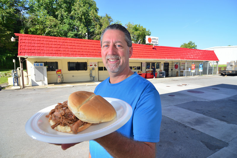Apple Shed is a convenient store owner Mark Winkler poses in front of the store holding a plate of BBQ. Photo by David Grace