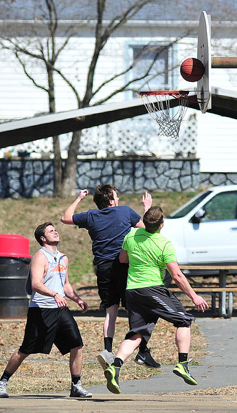 A group of men take advantage of the warm weather for a pick up basketball game at Borden Park Monday. Photo by David Grace