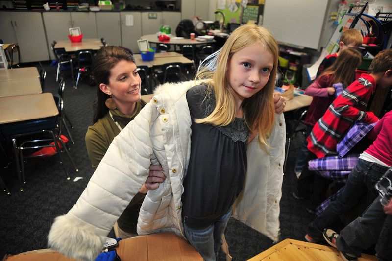 Jackson Elementary third grade teacher Caylor Harrison fits Lilly Miller with one of the almost 600 coats, donated to students at Jackson by various business people in cooperation Hamrick's Department Store. Photo by David Grace