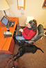 Contact Concern volunteer Patty Fletcher takes calls with  her seeing eye dog Campbell by her side. Photo by David Grace