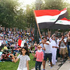 2014 Lowell Folk Festival. Iraqi immigrants wave flags as International Institute groups representing different countries are introduced at Boarding House Park. (SUN/Julia Malakie)