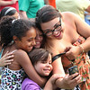 2014 Lowell Folk Festival. Clockwise from right: Annette Collazo of Lowell and her children Laelab Lefebvre, 4, Arianna Carrion, 9, and Reme Lefebvre, 10,  participate as everyone at Boarding House Park is instructed to take a 'selfie.' (SUN/Julia Malakie)