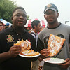 2014 Lowell Folk Festival. Salim Jalloh, left, and Ndeiiva Mason, right, both of Lowell, eating fried dough (with cinnamon and sugar) from the St. George Antiochian Church Middle Eastern food booth. (SUN/Julia Malakie)