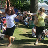 2014 Lowell Folk Festival. Joanne McArdle of Reading and her friend Charlene Trebach of Tyngsboro, right, lead a line dance as Egyptian Celebration musicians and members of Greek group Seizmos play during an Eastern Mediterranean music workshop at St. Anne's Churchyard.  (SUN/Julia Malakie)