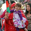 2014 Lowell Folk Festival. Manja Bilal of Lowell, holding daughter Isra Bilal, 1-1/2, march in the parade down Merrimack Street. They are originally from Afghanistan. (SUN/Julia Malakie)