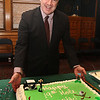 Official farewell party for outgoing Lowell city manager Bernie Lynch. Lynch poses for a photo by his cake. (SUN/Julia Malakie)