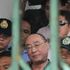 Authorities lead Globe Asiatique's Delfin Lee out of the court to the temporary detention cell at the NBI regional office in Pampanga on Friday. (Chris Navarro)