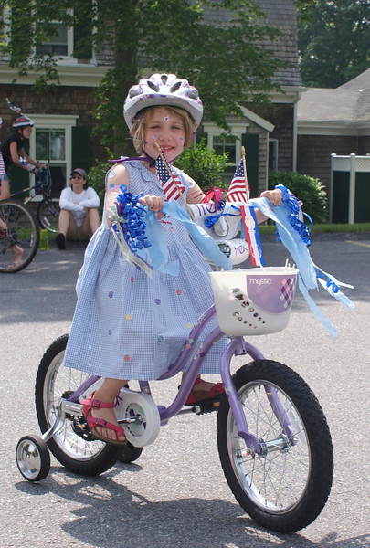 Emiliabianca Livia Pisani Ricciarini, age 6 from Cotuit sets out on her bike to participate in the  Cotuit Fourth of July Parade which has taken place every year since 1976. It is organized by the Cotuit Civic Association.
