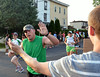 A spectator offers a high-five to a runner approaching the finish line of the Tex Mex 5K Race for Open Space in North Wales.    Wednesday, June 25, 2014.   Photo by Geoff Patton
