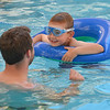 Alex Schmitt, 6,right,  swims in an inner tube toward instructor Davis Turner for a rescue technique demonstration during the World's Largest Swim Lesson at the Broomfield Academy on Thursday.<br /> <br /> June 14, 2012 <br /> staff photo/ David R. Jennings