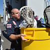North Metro Fire Rescue firefighter David Alizer carries a bin full of lacrosse sticks while unloading a semi truck from Ball Corp. with 5,000 cubic feet of sports equipment for the Jessica Redfield Ghawi giveSports Scholarship Fund at A Precious Child on Saturday. September 8, 2012 staff photo/ David R. Jennings