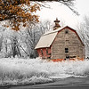 Conspiracy of Nature - The seasons overlap as autumn leaves give way to winter snow, but the creaking, red barn continues to stand for another day.
