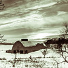 Sunset Over the Glade: In Shades of Grey - The old barn tries to burrow its way into the snow-covered hillside as the watery winter sun sets over its head.