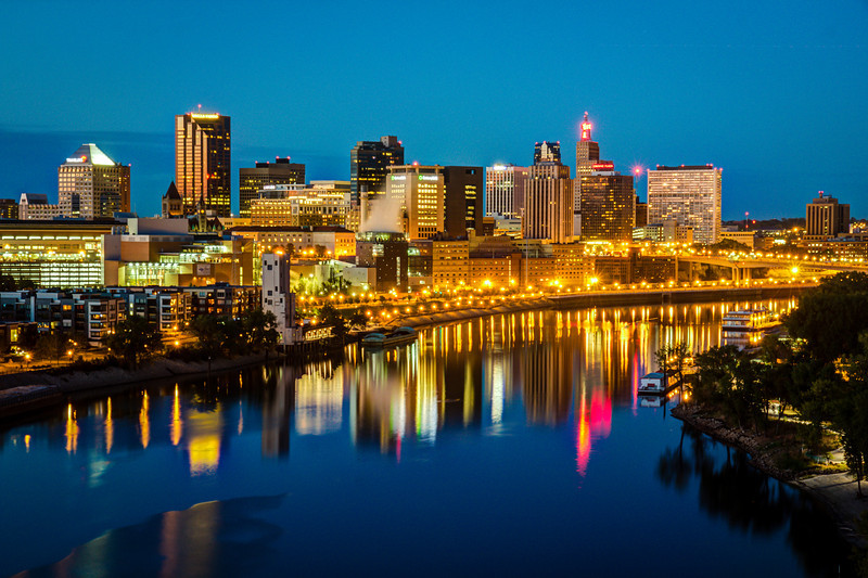 Saint Paul at Night - In Technicolor.  The golden glow of the night skyline of St. Paul is bracketed by the turquoise sky above and the midnight blue river below.