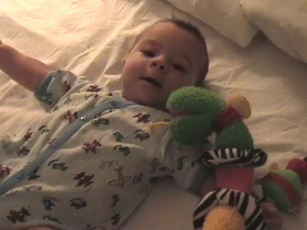 2002-7-19 - Ian on bed with caterpillar toy