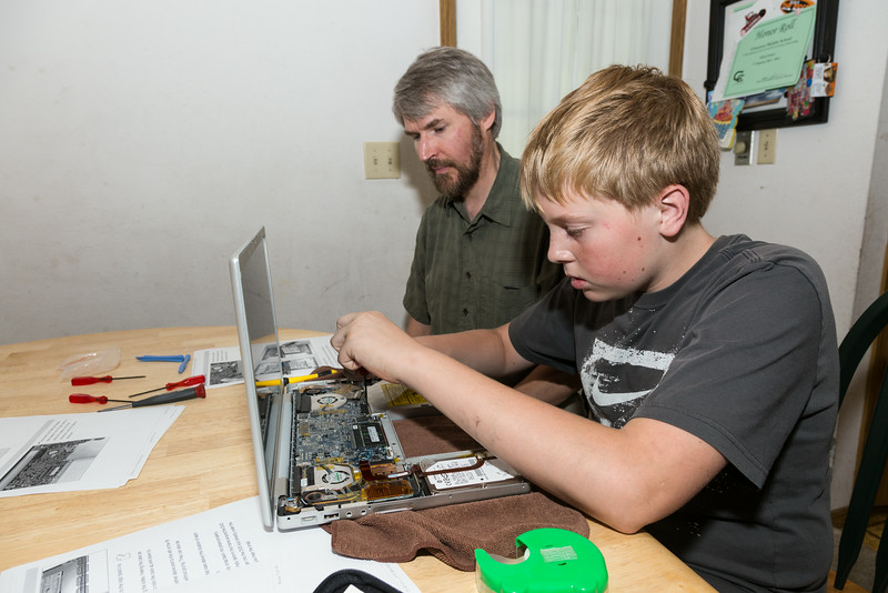 """Electronics Whizzes""<br /> <br /> James looks at instructions and lends his expertise while grandson, A, age 12, works on his MacBook Pro computer. A was disassembling the computer to remove the motherboard, which was fried."