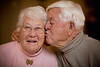 An elderly man kissing his wife.