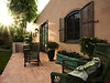 Side view of patio area with green wicker chairs, brick floor, rustic style window shutters, southwestern house exterior, planter, and the sunlight peaking through the trees.