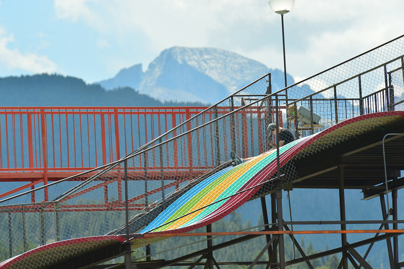 A young man sits on the famouns rainbow slide while waiting for customers. The slide is nearly as iconic to Estes Park as the towering peak to the south.