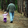 Father and toddler walk in the woods.