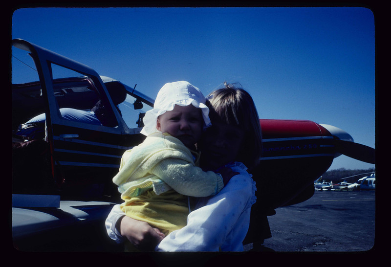 Circa early 80s/ Lisa holding Laura Bradley at Wings Field waiting to fly down to Bermuda in the family plane. That's Alix Moriarty in teh back seat.