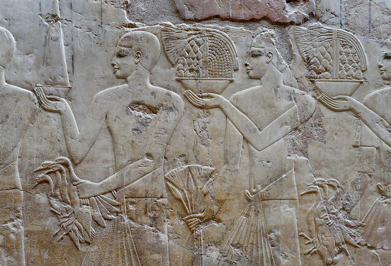 "[EGYPT 29336] Bearers of offerings in Ramose's tomb at Luxor.'  	A relief in Ramose's tomb shows bearers of offerings such as lotus flowers, waterfowl and bowls with figs, pomegranates and a pointed bread. Ramose was an 18th dynasty 'Governor of the Town' (of Thebes) and Vizier during the transition of the reigns of Amenhotep III and Echnaton. His tomb (TT 55) is located in the Sheikh Abd el Qurnah Necropolis on the Westbank at Luxor and is one of the socalled ""Tombs of the Nobles"". It is uncertain whether he was ever buried in this tomb or that he followed Echnaton to his new capital near Amarna and was buried there. Photo Mick Palarczyk and Paul Smit."