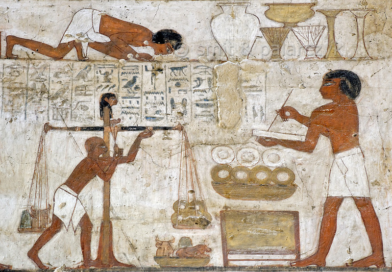 "[EGYPT 29357] 'Weighing gold and silver in Rekhmire's tomb at Luxor.'  	A mural in the tomb of Rekhmire shows several scenes representing the types of labor carried out by craftsmen who worked for the Amon Temple in Karnak. Here we see the weighing and recording of gold and silver (in the form of rings) collected as taxes. The weights have been given the form of a bull's head and a hippo. The top of the balance is decorated with the head of the Goddess of Truth, Maat, to ensure honesty and accuracy. Rekhmire was an 18th dynasty vizier (viceroy) of Southern Egypt, mayor of Thebes and steward of the Amon Temple at Karnak during the reigns of Thutmosis III and Amenhotep II. His tomb (TT 100) is located in the Sheikh Abd el Qurnah Necropolis on the Westbank at Luxor and is one of the socalled ""Tombs of the Nobles"". Photo Mick Palarczyk and Paul Smit."