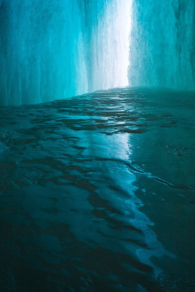 """ICE PORTAL""  Minneapolis, Minnesota  Behind Minneapolis' famous Minnehaha Falls exists a mesmerizing world of ice. The frozen falls reflect blue light in every direction, creating a beautiful and surreal space."