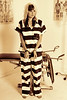 Studio shot, beautiful girl in prison outfit and cuffs handcuffs