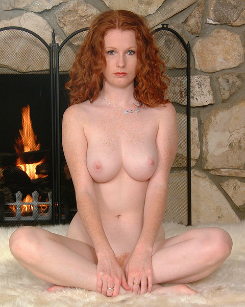 Busty nude redhaired girl on carpet in front of fireplace