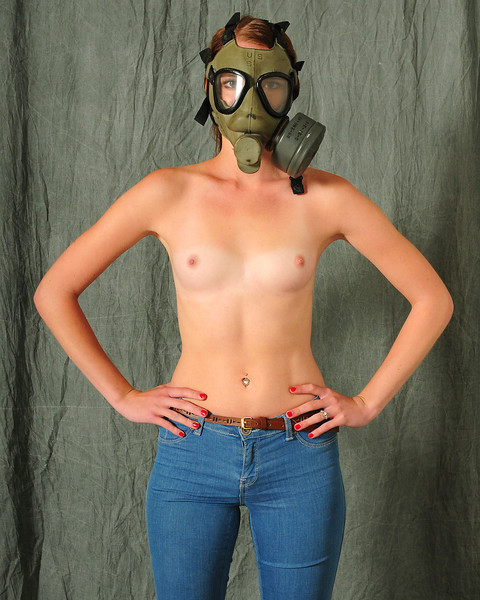 Topless bare-breast semi-nude girl wears gasmask in studio photo