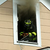 A firefighter takes a moment up in the attic window to talk to the Chief below<br /> <br /> Photo Scott LaPrade