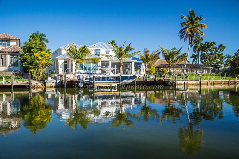 Reflections of a canal-side home with pleasure boats in Naples, Florida, USA.