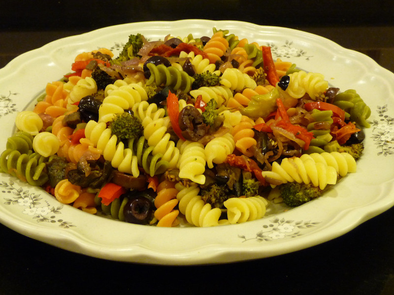 Pasta with Roasted Vegetables A very simple, low fat, tasty meal.  Roast your choice of veggies.  To roast veggies, toss a bunch of veggies with 1 or 2 tablespoons of olive oil, spread out in a single layer and bake at 425°F for 30 minutes or so --- realize they will reduce significantly in volume ... if you start with 4 cups of veggies, you'll end up with closer to 2 cups.  Stir every 5-10 minutes while they are roasting.   To make this totally fat free, toss your veggies with a fat free Italian Dressing .... this actually adds more flavor than the olive oil.  Recipe for a fat free Italian Dressing here.  When they are just starting to brown, remove from oven and toss with hot pasta.  If desired, drizzle with about a Tablespoon of olive oil per serving, but the veggies are flavorful enough that this isn't necessary if you are watching fat intake.  Any veggies will work fine ... I think this batch has broccoli, red peppers, onions, and garlic.  I also added sun dried tomatoes and olive slices to the veggies after roasting them.  For gluten free folks, use a gluten free pasta ... there are several good choices of rice pasta available right now that cook up firm and tasty.