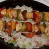Mixed skewers of a bed of Dirty Rice