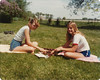 Becky Warner and Linda Summers playing backgammon on mom and dad's front yard on farm.