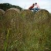 Couple kisses on hay bales