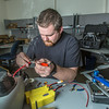 """Technician Michael Cook works on one of the unmanned aerial vehicles in UAF's Alaska Center for Unmanned Aircraft Systems Integration (ACUASI) shop in south Fairbanks.  <div class=""""ss-paypal-button"""">Filename: AAR-13-4026-24.jpg</div><div class=""""ss-paypal-button-end""""></div>"""