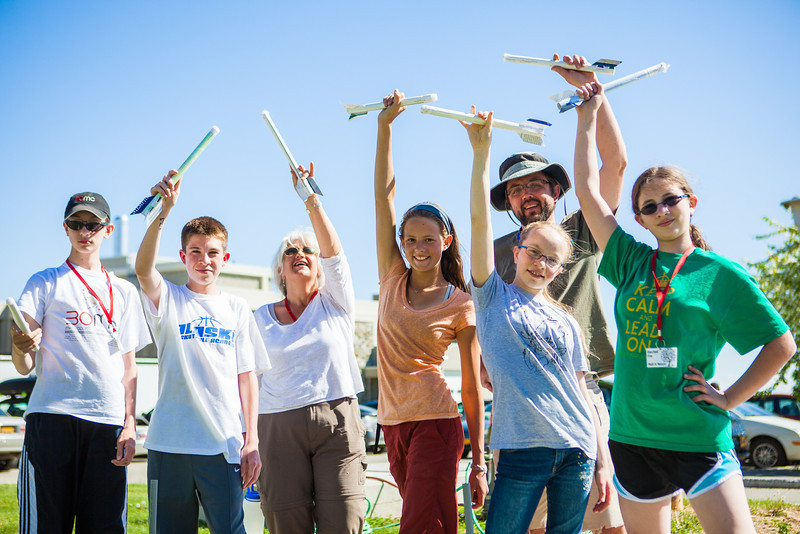 Rockets on hand, middle school students pose for a picture after trying various rocket designs outdoors during the Alaska Summer Research Academy.  Filename: AAR-13-3862-48.jpg