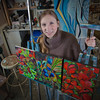 Art major Klara Maisch poses with some of her paintings in the Fine Arts studio.  Filename: AAR-12-3299-57.jpg