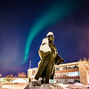 "A strand of light from the aurora borealis floats above the statue of Charles Bunnell and the Bunnell Building on the Fairbanks campus.  <div class=""ss-paypal-button"">Filename: CAM-13-3724-11.jpg</div><div class=""ss-paypal-button-end"" style=""""></div>"