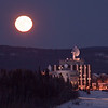 A full moon rises over the hill behind UAF's West Ridge on a cold January afternoon.