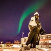 "A strand of light from the aurora borealis floats above the statue of Charles Bunnell and the Bunnell Building on the Fairbanks campus.  <div class=""ss-paypal-button"">Filename: CAM-13-3724-9.jpg</div><div class=""ss-paypal-button-end"" style=""""></div>"