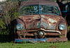An old rusty car sits abandoned in a field