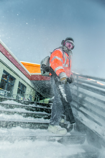 """A groundskeeper on the Facilities Services crew clears campus steps and sidewalks after a February morning snowfall.  <div class=""""ss-paypal-button"""">Filename: LIF-14-4072-35.jpg</div><div class=""""ss-paypal-button-end""""></div>"""