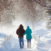 A couple make their way to the Commons while brisk winds created snow drifts during a heavy February snowfall on the Fairbanks campus.  Filename: LIF-11-2992-012.jpg