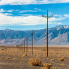 Row of power line poles in the foothills of Sierra Nevada Mountains, California