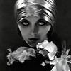 Actress Pola Negri wearing a lam� headwrap, with flowers in front of her